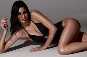 Kendall Jenner black swimsuit laying on side